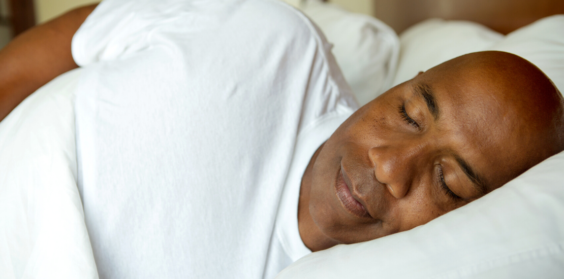 A black man of middle age, asleep in bed