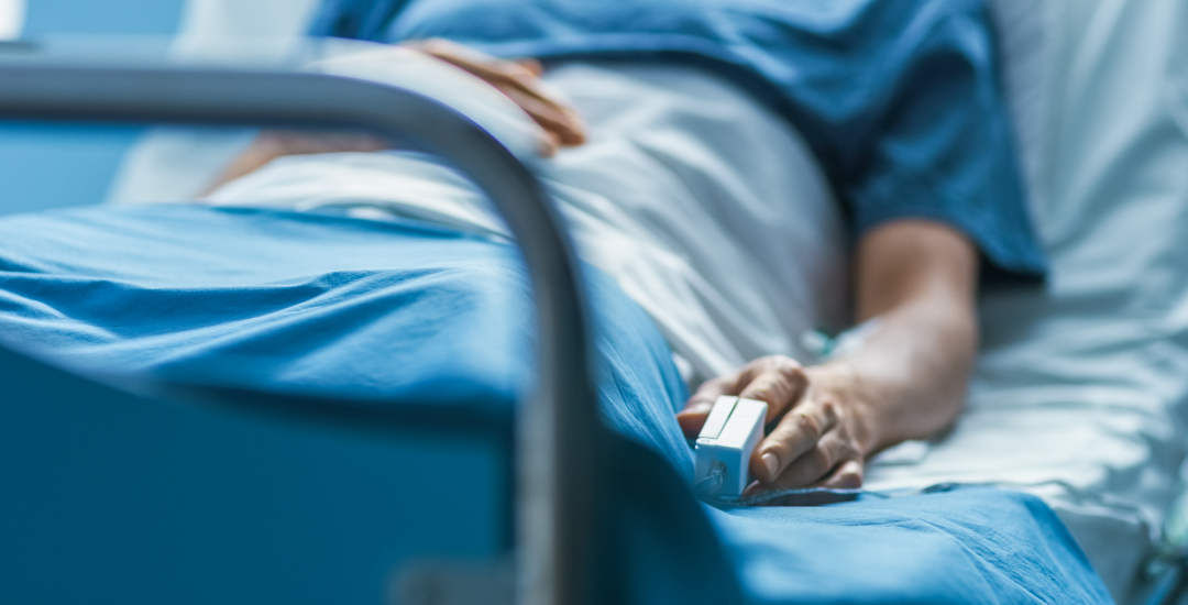 A patient lying in a hospital bed, with an oxygen monitor on their finger